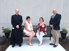 "Photo of Father Michael Driscoll, Cherie Reynolds, OSF Foundation, Holly Grobe, wife of the late Gene Grobe, and Ken Beutke, President of OSF Saint Elizabeth Medical Center, sitting on the Eugene ""Gene"" Grobe Memorial Bench."