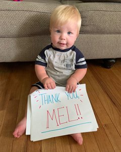 A photo of Jack holding a sign thanking Mel for her care.
