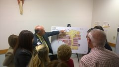 Ken Beutke, President, showing facility renderings to community members.